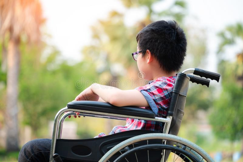 Самостоятельно молодой неработающий человек на кресло-коляске в парке, пациент ослабляет в украшениях сада чувства больницы пропу стоковая фотография rf