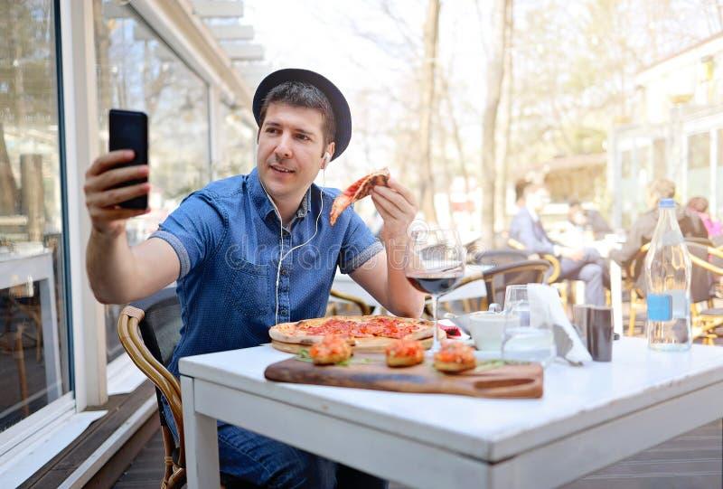 Самостоятельно туристский человек принимая selfie и есть кусок пиццы стоковое изображение rf