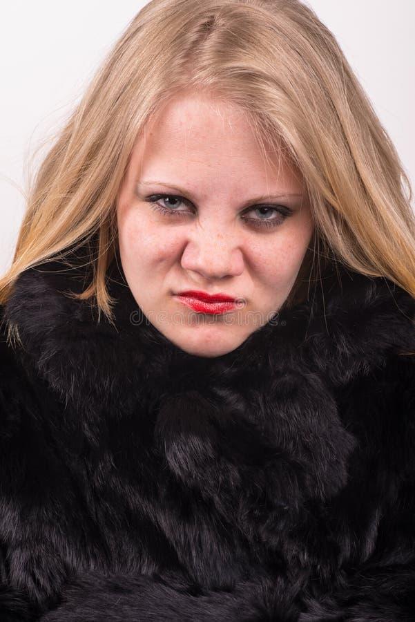 Самоуверенная сердитая молодая милая молодая женщина в куртке шерсти стоковые фото
