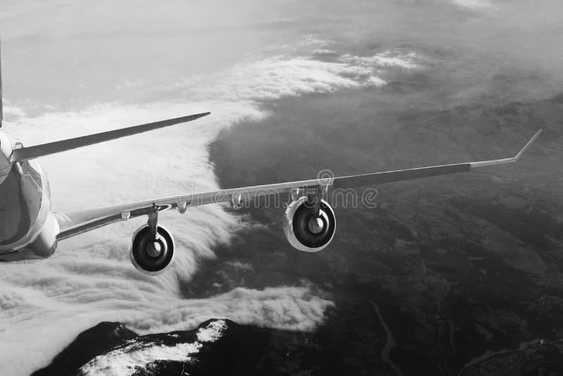 Самолет в белизне черноты предпосылки самолета перехода перемещения полета неба стоковая фотография