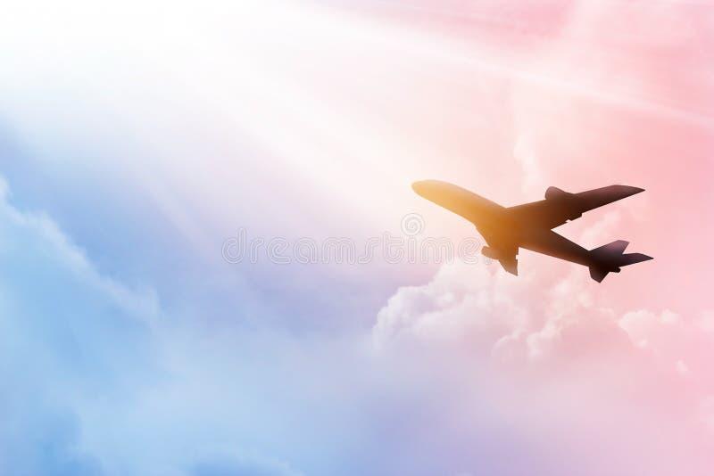 Самолет в небе и облаке красочных на заходе солнца стоковое фото