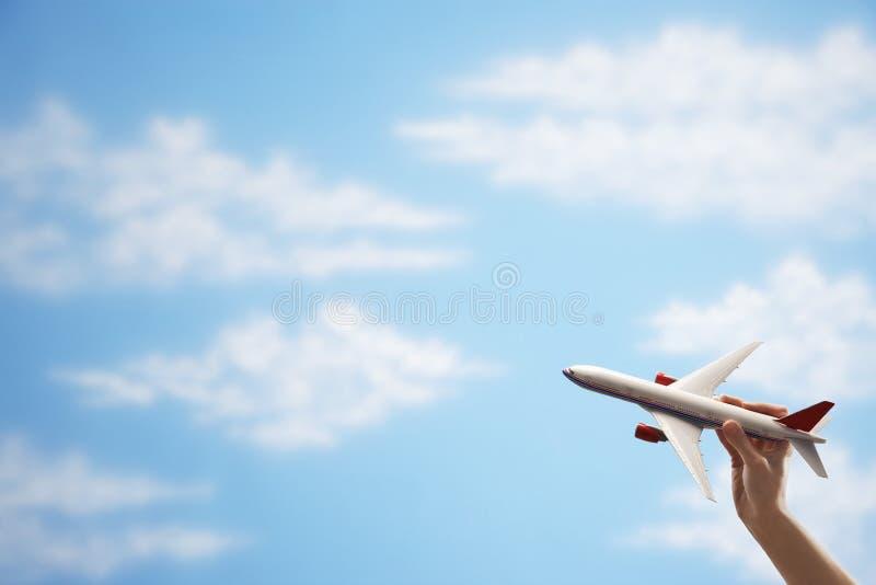 Самолет игрушки летания руки против неба стоковое изображение rf