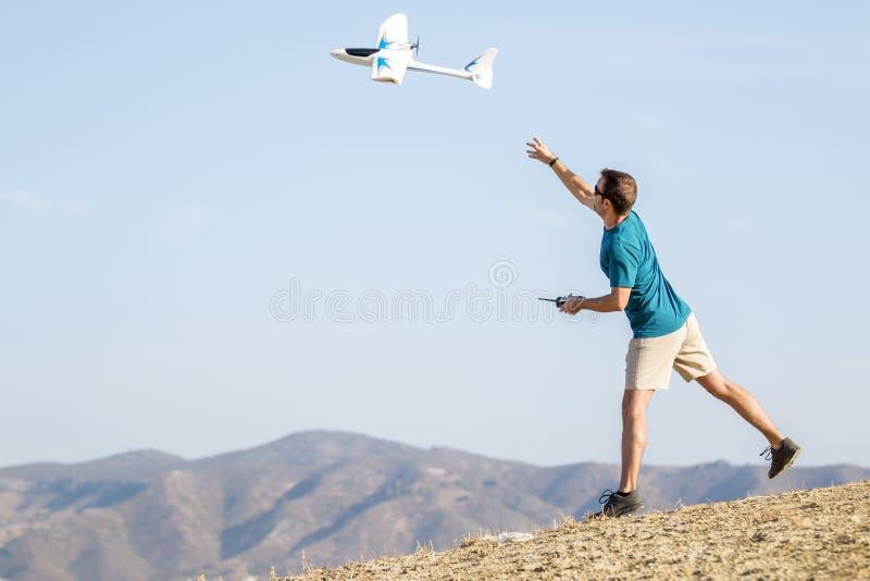 Самолет дистанционного управления установки молодого человека в воздухе стоковые фото
