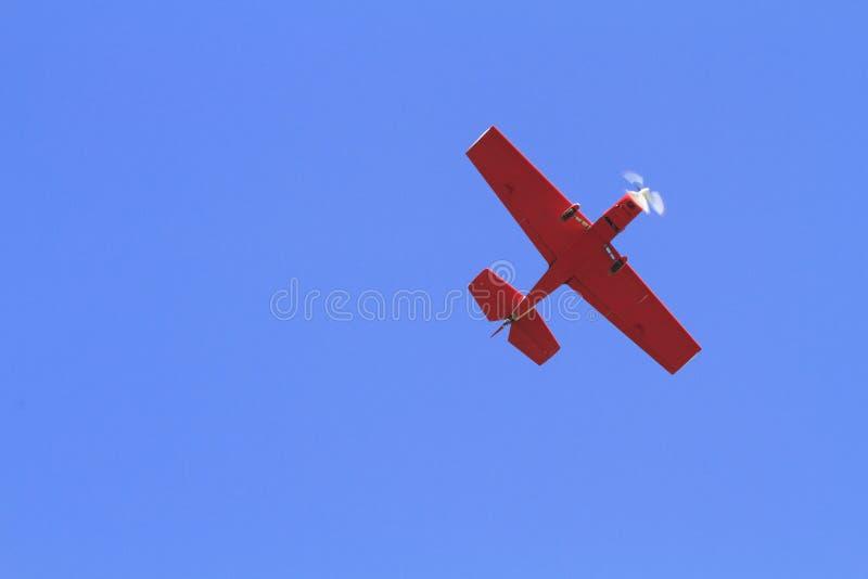 Самолет красного цвета на голубом небе стоковое фото