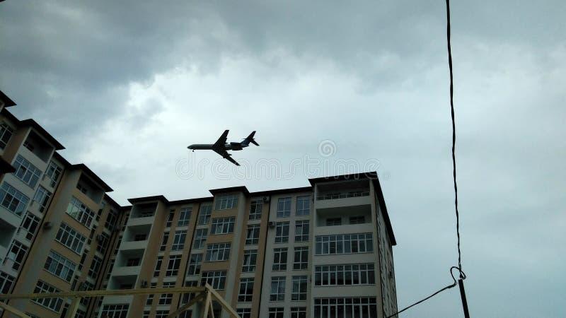 Самолет над городом стоковая фотография