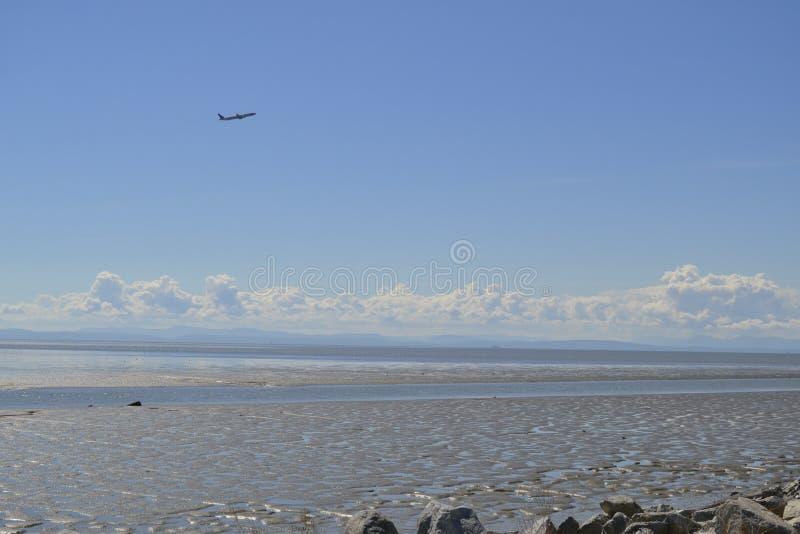 Самолет над океаном стоковая фотография