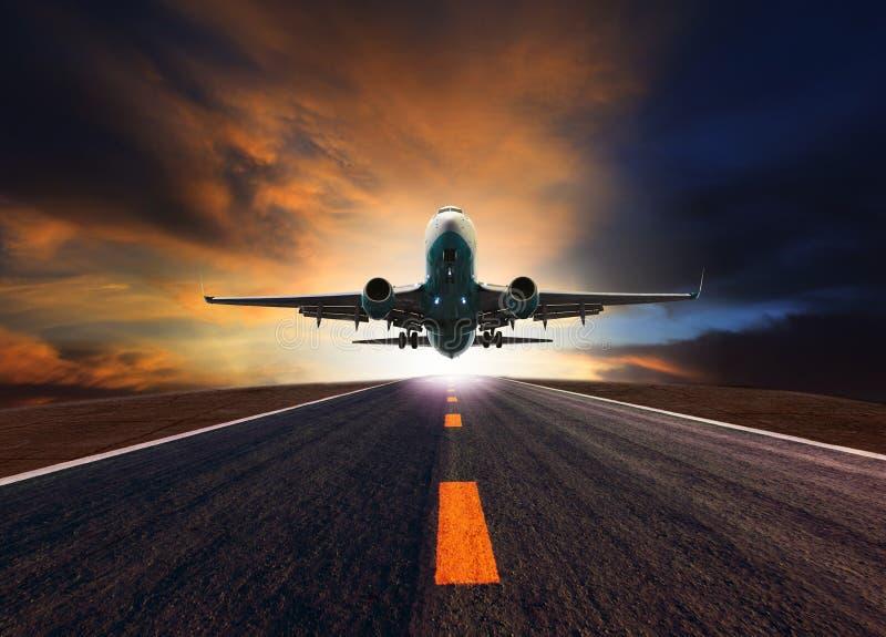 Самолет пассажирского самолета летая над взлётно-посадочная дорожка авиапорта против красивого стоковое фото