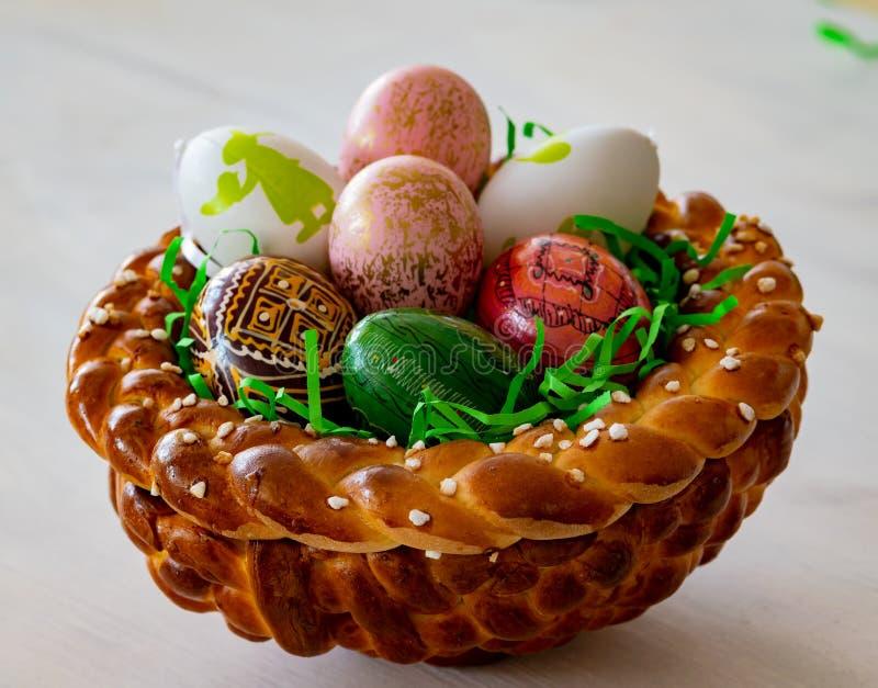 Само-испеченное и форменное гнездо пасхи сделало из теста дрожжей с красочными пасхальными яйцами стоковые фото