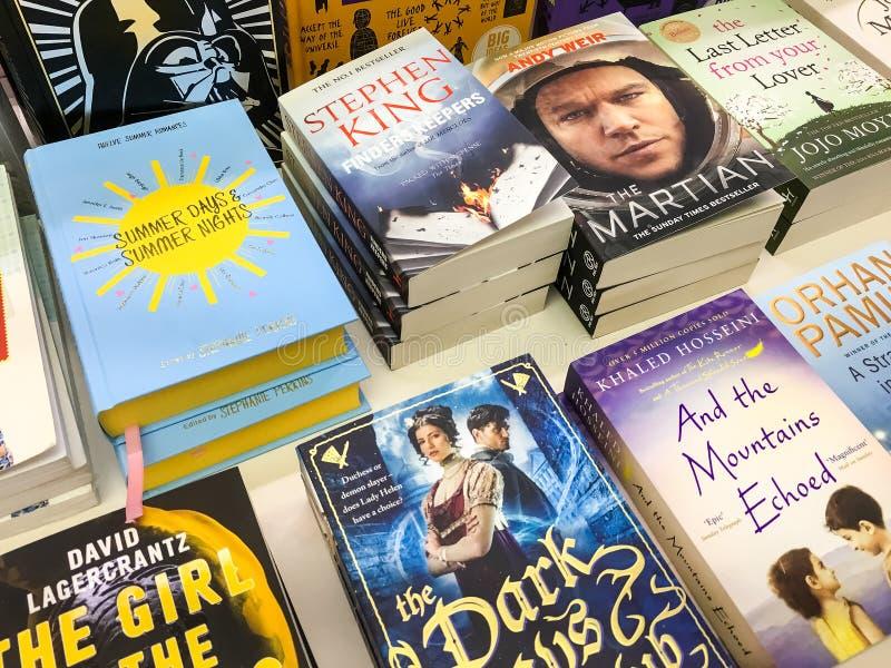Самые последние английские известные романы для продажи в книжном магазине библиотеки стоковое изображение