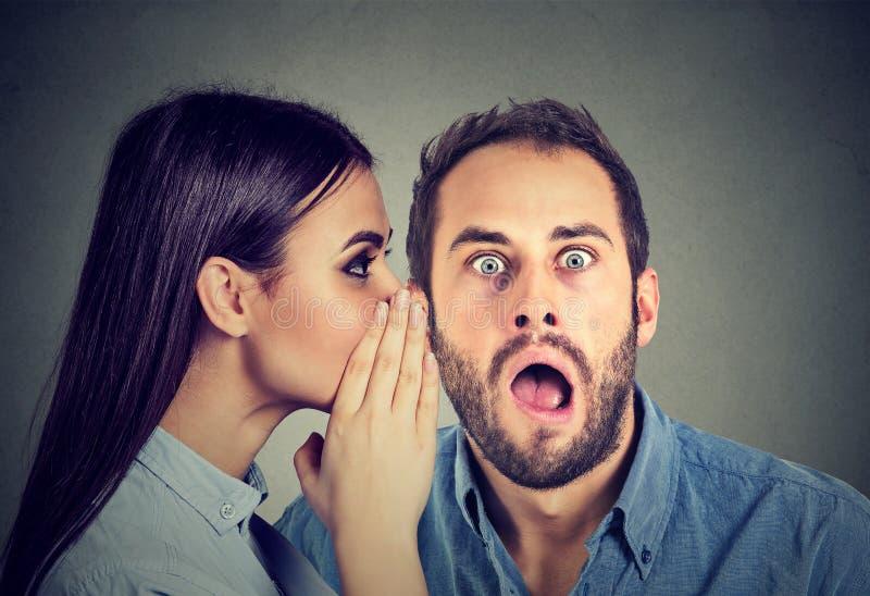 самые последние молвы Изумленная сплетня человека слушая в ухе стоковые фото