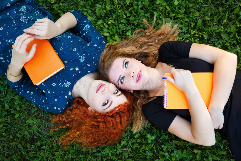 Самые лучшие подруги студенты на лужайке стоковые изображения