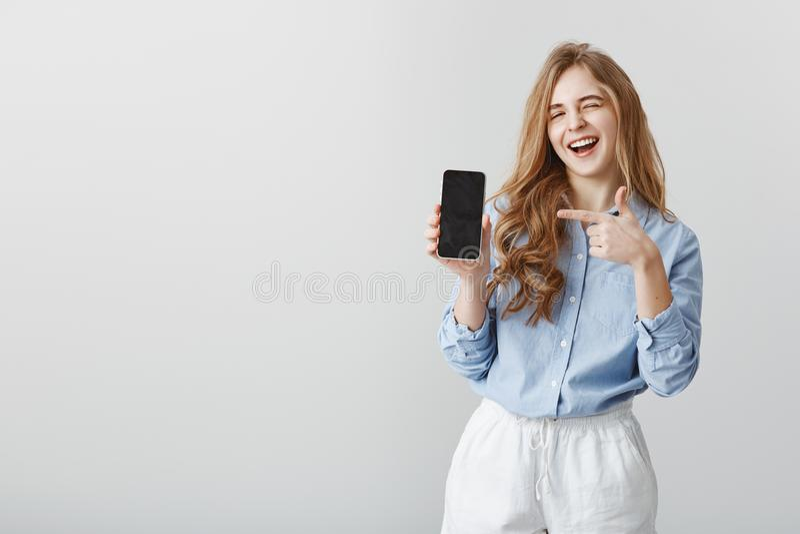 Самый лучший выбор всегда Портрет симпатичной кавказской женской модели с светлыми волосами в голубой блузке, подмигивая и усмеха стоковые фотографии rf