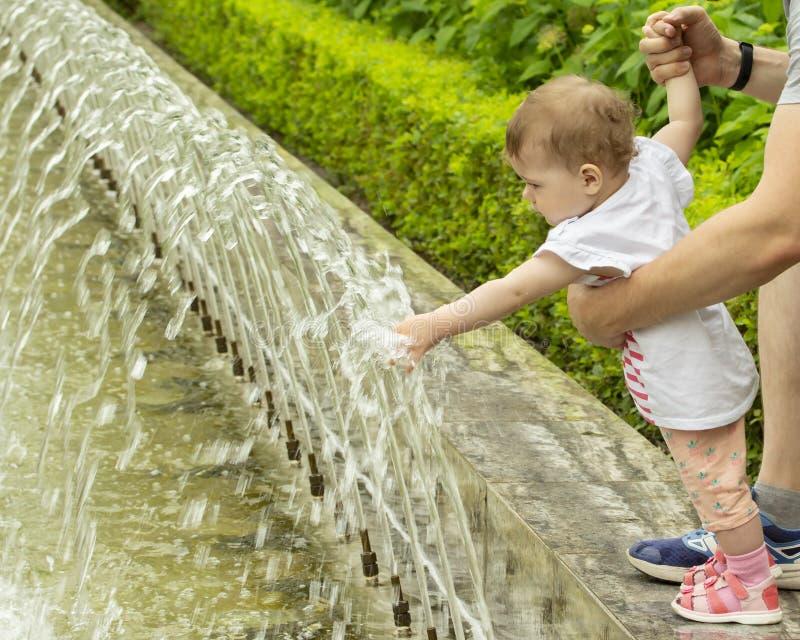 Сандалии пинка младенца играя с водой Младенец касается воде в фонтане, впихывает руки под двигателями воды Девушка в стоковое изображение