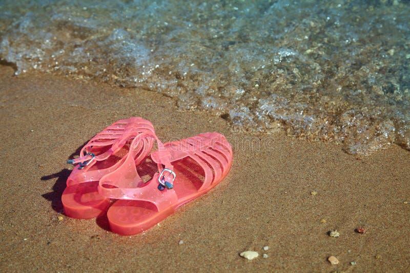 САНДАЛИИ СТУДНЯ розовых женщин на береге моря КВАРТИРА ДАМ ПРЕВРАЩАЕТ В ЖЕЛЕ БОТИНКИ ПЛЯЖА ЛЕТА стоковые фотографии rf