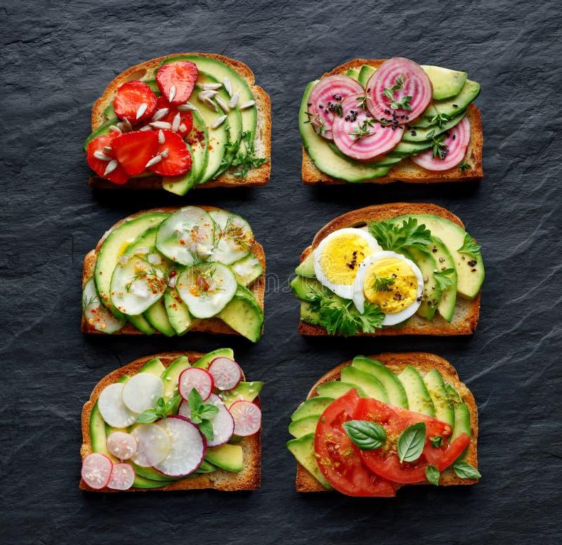 Сандвичи авокадоа, здравицы с различными вегетарианскими отбензиниваниями на черной каменной предпосылке стоковая фотография