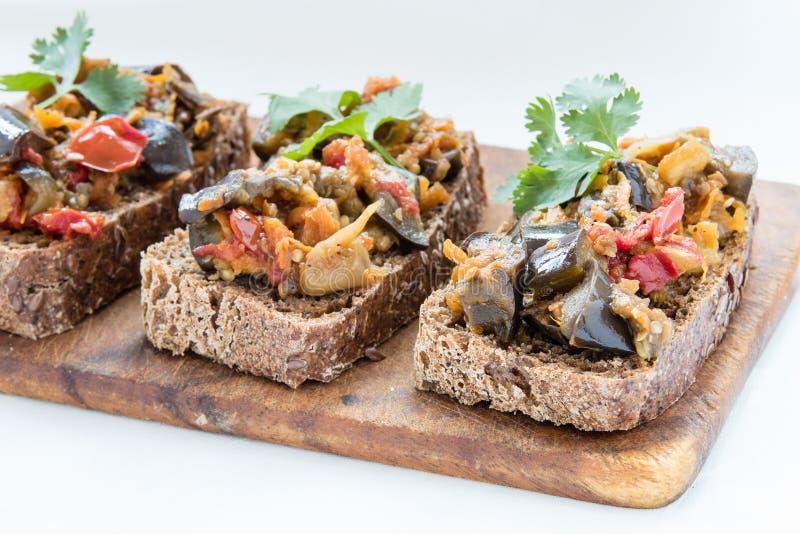 Сандвичи с листьями икры и петрушки баклажана на деревянной доске стоковые изображения rf