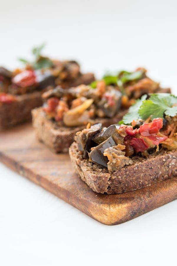Сандвичи с листьями икры и петрушки баклажана на деревянной доске стоковое фото rf