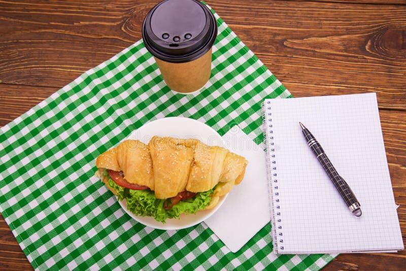 Сандвич круассана на поддоннике Блокнот и ручка на деревянном tabl стоковое изображение rf