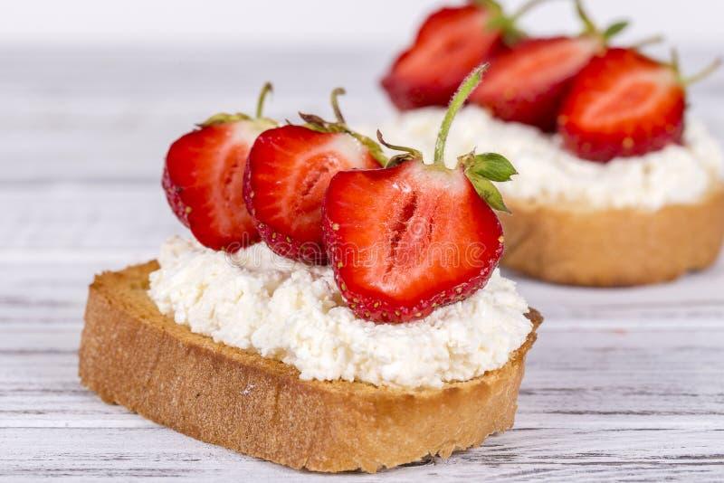Сандвич 2 от красной клубники, белого творога и хлеба на белом деревянном столе, конца вверх стоковая фотография