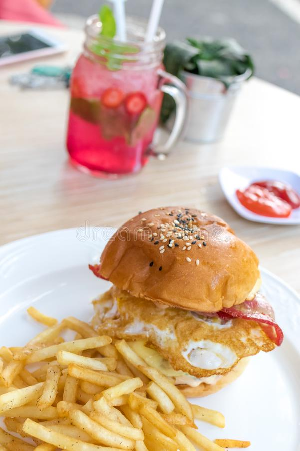 Сандвич с фраями бургера, томатов, сыра, салата и француза цыпленка Лимонад клубники на backgorund снаружи стоковое изображение rf
