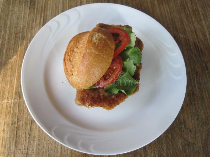 Сандвич Escalope/шницеля с томатами и салатом стоковое изображение rf