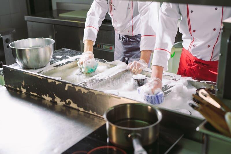 Санитарный день в ресторане Повторения моют ваше рабочее место Повара моют печь, плиту и экстрактор в ресторане стоковая фотография rf