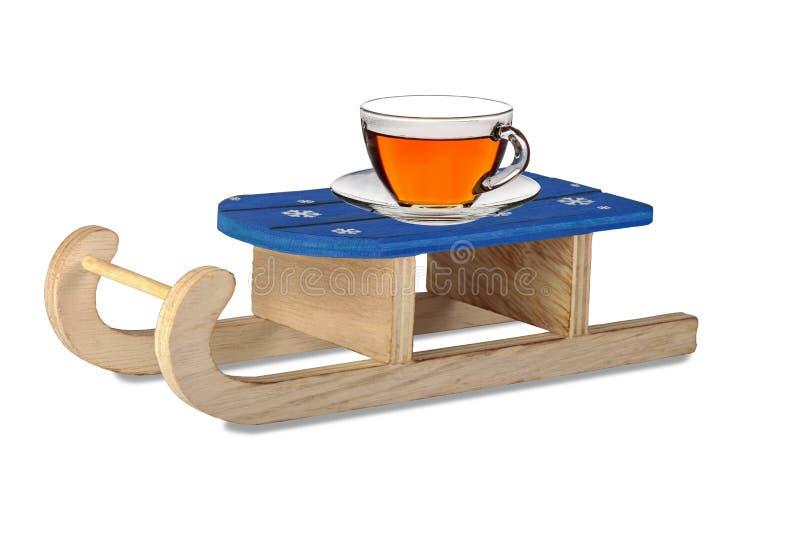 Сани и чай зимы в стеклянной чашке на поддоннике коллаж стоковые изображения rf