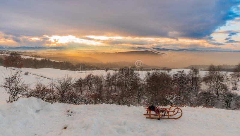 Сани неба и захода солнца горы зимы красочные на переднем плане стоковое фото