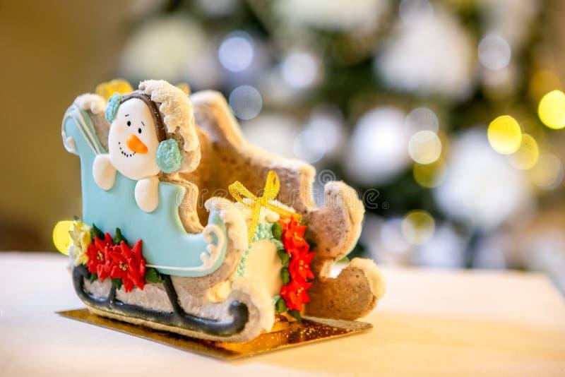 Сани пряника со снеговиком перед defocused светами ели украшенной рождеством Помадки праздника Новый Год и стоковая фотография