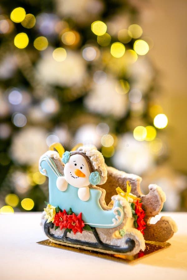 Сани пряника со снеговиком перед defocused светами ели украшенной рождеством Помадки праздника Новый Год и стоковое изображение