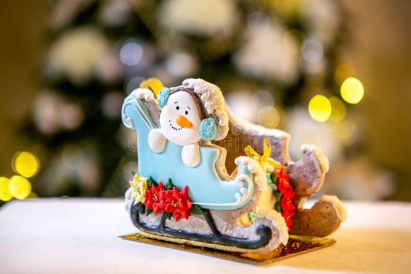 Сани пряника со снеговиком перед defocused светами ели украшенной рождеством Помадки праздника Новый Год и стоковые изображения