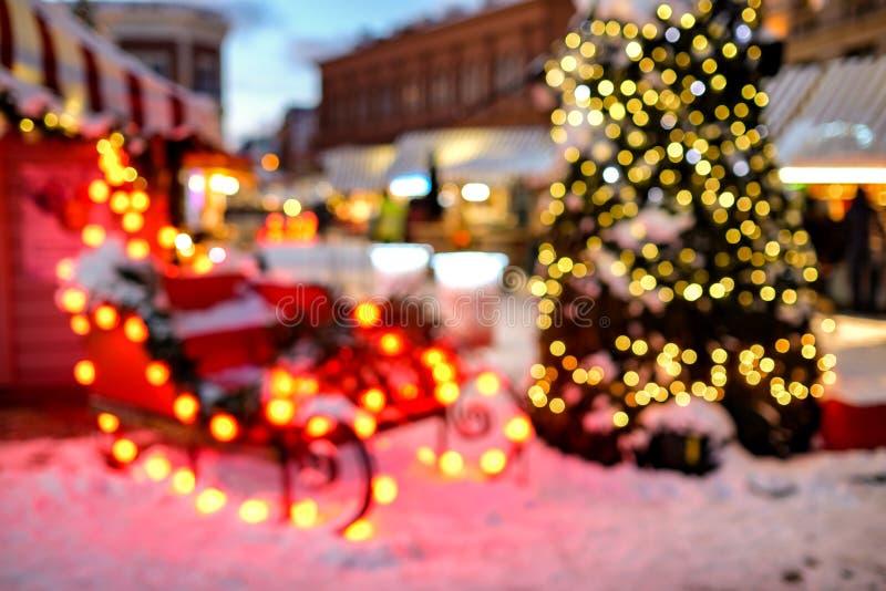 Сани ` s Санта Клауса и дерево Christmass в светах bokeh Справочная информация стоковые фото