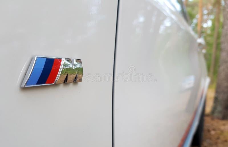САНКТ-ПЕТЕРБУРГ, РОССИЯ: Взгляд со стороны символа бренда BMW X5M в лесе на 20-ое июля 2018 стоковые фото