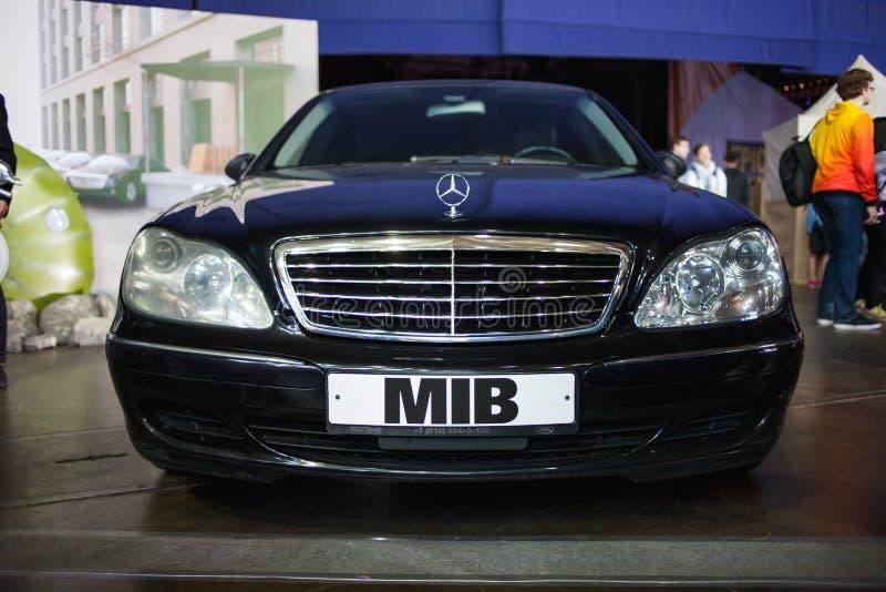 САНКТ-ПЕТЕРБУРГ, РОССИЯ - 27-ОЕ АПРЕЛЯ 2019: человек в черном, черном автомобиле с MIB логотипа стоковое изображение rf