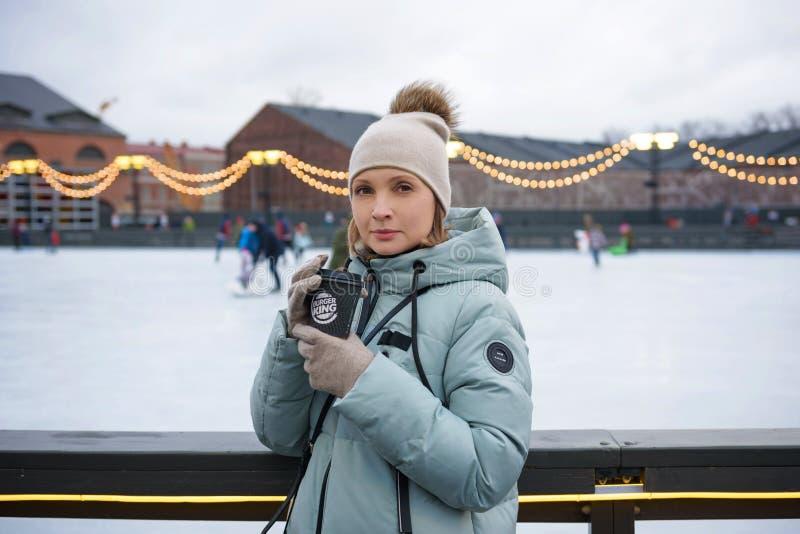 Санкт-Петербург, РОССИЯ - 18-ое декабря 2018: девушка выпивает горячий кофе на предпосылке катка в бумажном стаканчике Burger Kin стоковое фото rf
