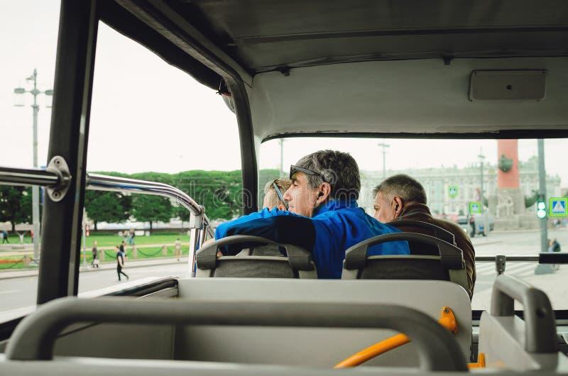 Санкт-Петербург, РОССИЯ - 8-ое июля 2018: Туристы идут к туристическому автобусу и смотрят вне окно Туризм в Санкт-Петербурге, Ро стоковое фото rf