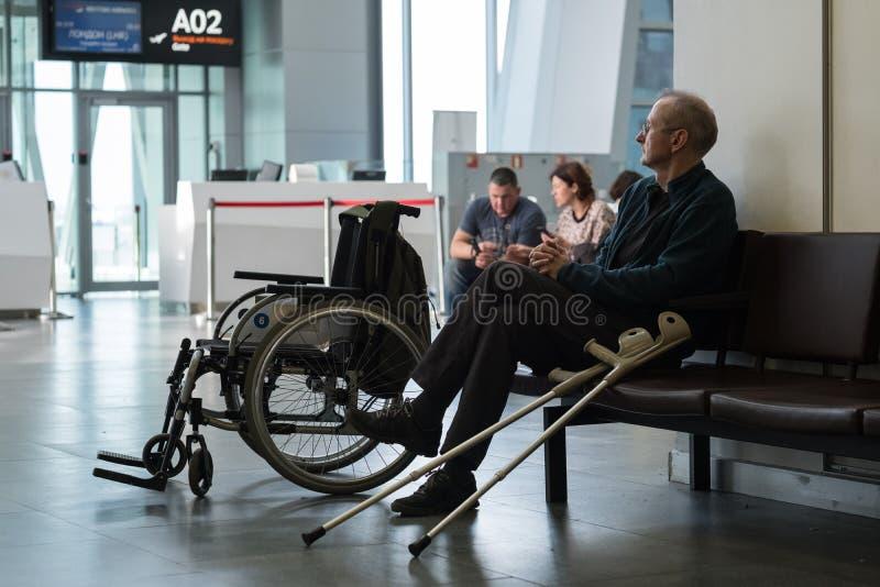 Санкт-Петербург, Россия - 8-ое октября 2018: Пожилой лысый инвалид в гостиной отклонения перед восхождением на борт самолета смот стоковые изображения