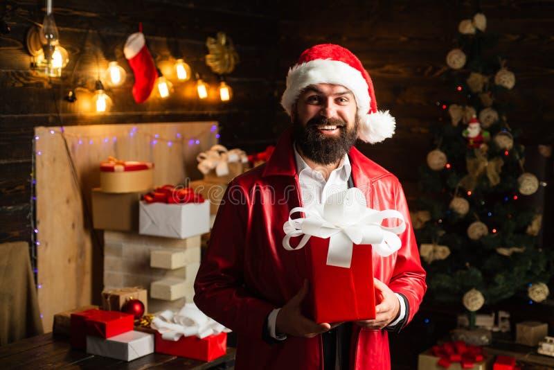 Санта Клаус в современной красной куртке С Рождеством Христовым и с новым годом Санта Клаус с красной подарочной коробкой рождест стоковые изображения rf