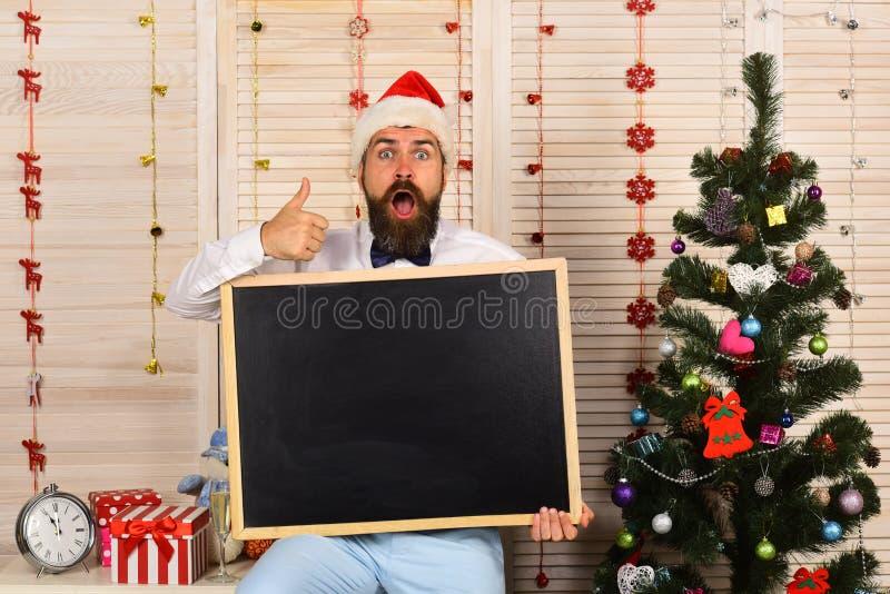 Санта Клаус в шляпе с сотрясенной стороной показывает большие пальцы руки вверх стоковая фотография rf