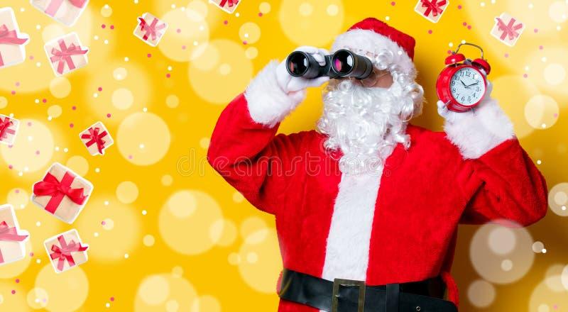 Санта Клаус держа бинокли и будильник стоковое изображение rf