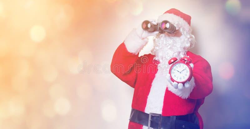 Санта Клаус держа бинокли и будильник стоковое фото