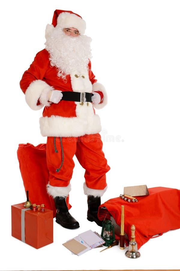 Санта Клаус держа между мешками, настоящими моментами и письмами стоковые фото