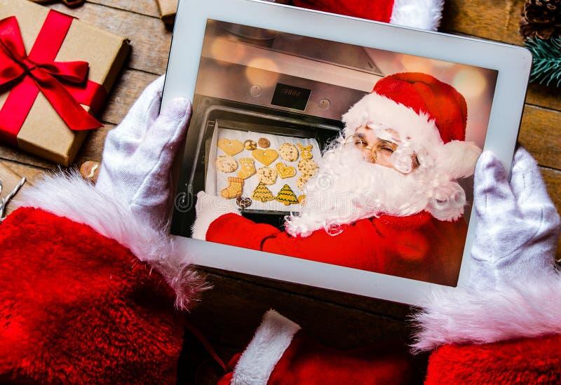 Санта Клаус держа прибор таблетки стоковые фото