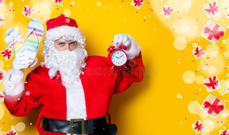Санта Клаус держа темповые сальто сальто и будильник стоковое фото