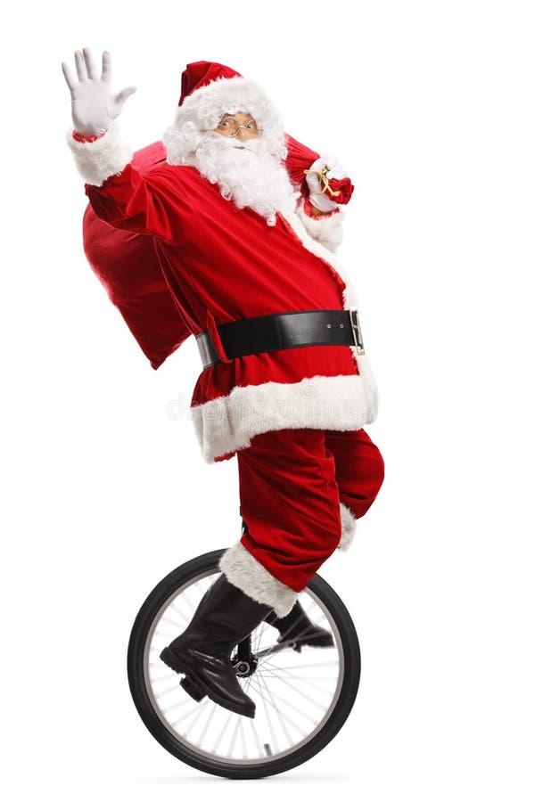 Санта Клаус ехать юнисайкл, развевая и нося мешок настоящих моментов стоковая фотография rf