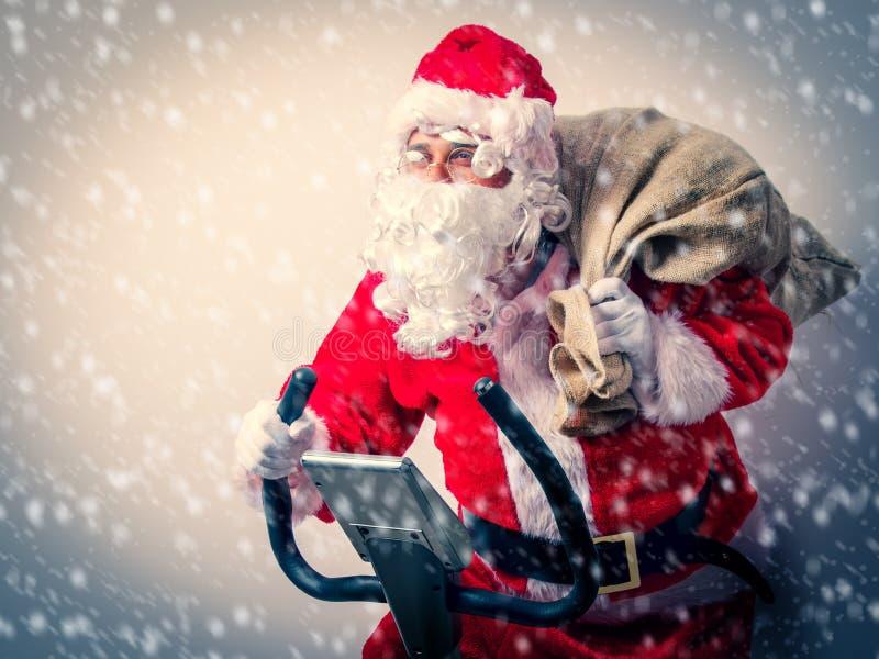 Санта Клаус имеет потеху с велотренажерами стоковое фото