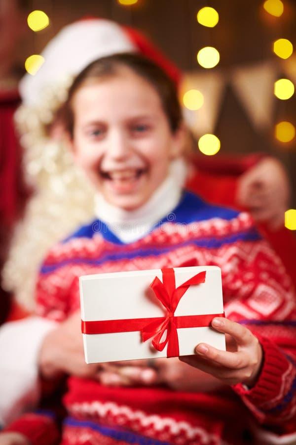 Санта Клаус и девочка, позирующие вместе в помещении рядом с украшенным крепостью, с огнями, разговаривают и улыбаются. стоковое изображение rf
