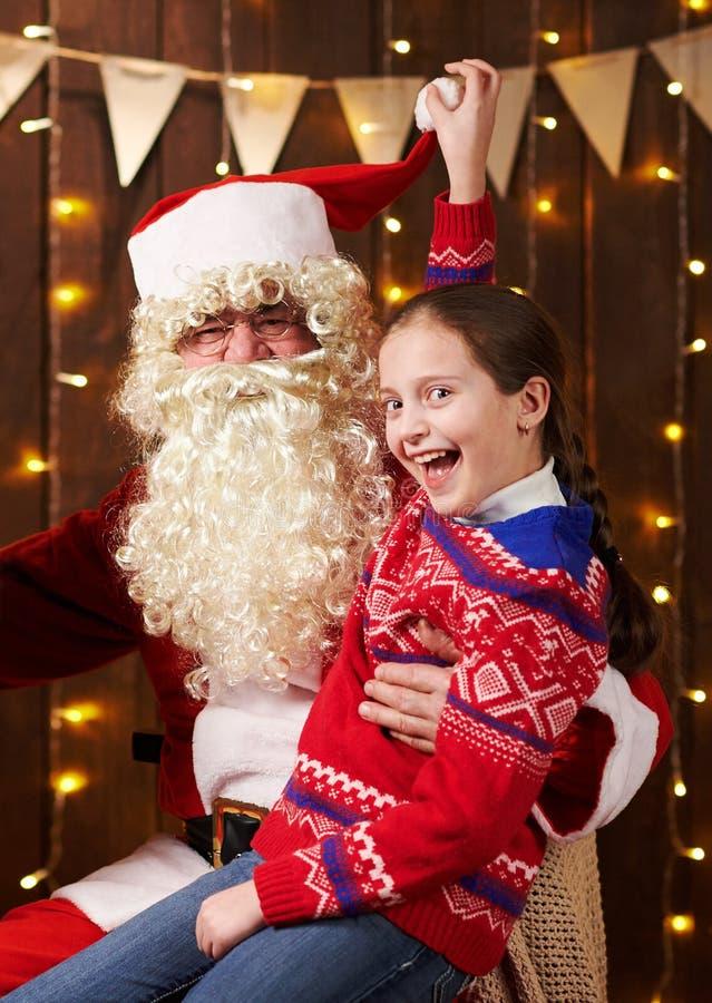 Санта Клаус и девочка, позирующие вместе в помещении рядом с украшенным крепостью, с огнями, разговаривают и улыбаются. стоковые изображения rf