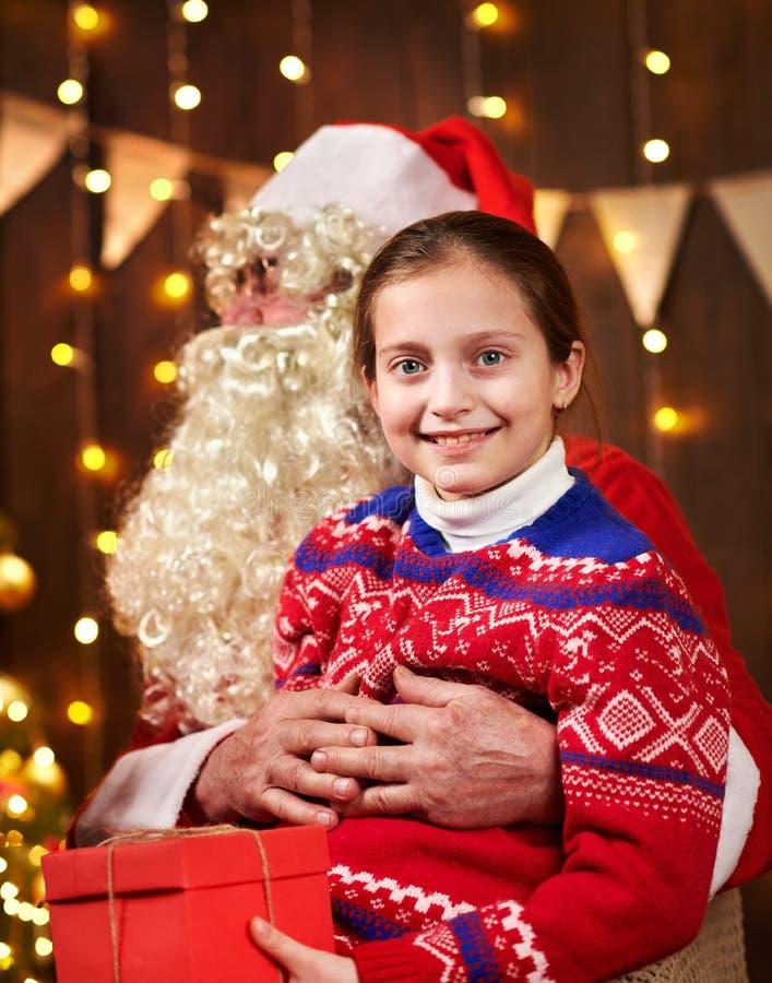 Санта Клаус и девочка, позирующие вместе в помещении рядом с украшенным крепостью, с огнями, разговаривают и улыбаются. стоковая фотография rf