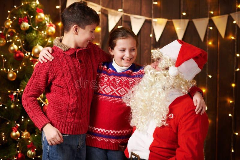 Санта-Клаус и мальчик и девочка, позирующие вместе в помещении, рядом с декорированным xmas деревом с огнями, разговаривают, улыб стоковая фотография